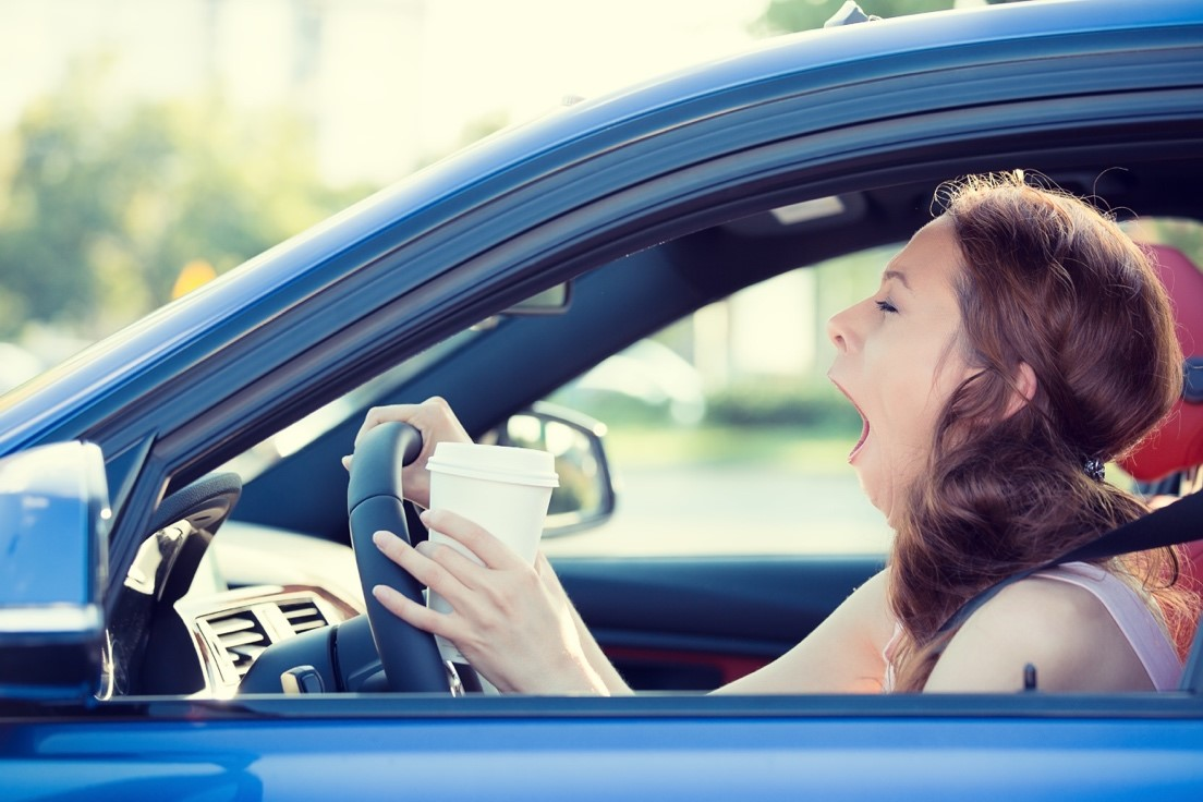Image of Distract Driving - driving women yawning while holding a coffee cup