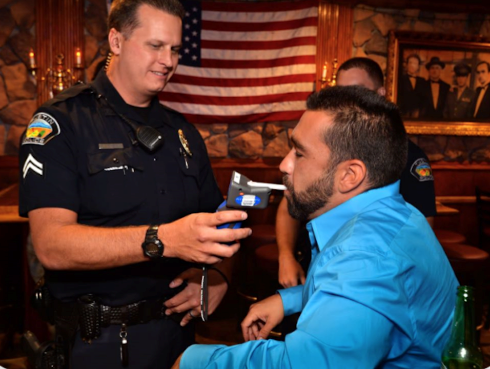 Person blowing into an alcohol volume testing device, or breathalyzer.