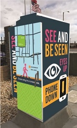 Traffic signal cabinet with the message See and Be Seen. Eyes Up, Phones Down.