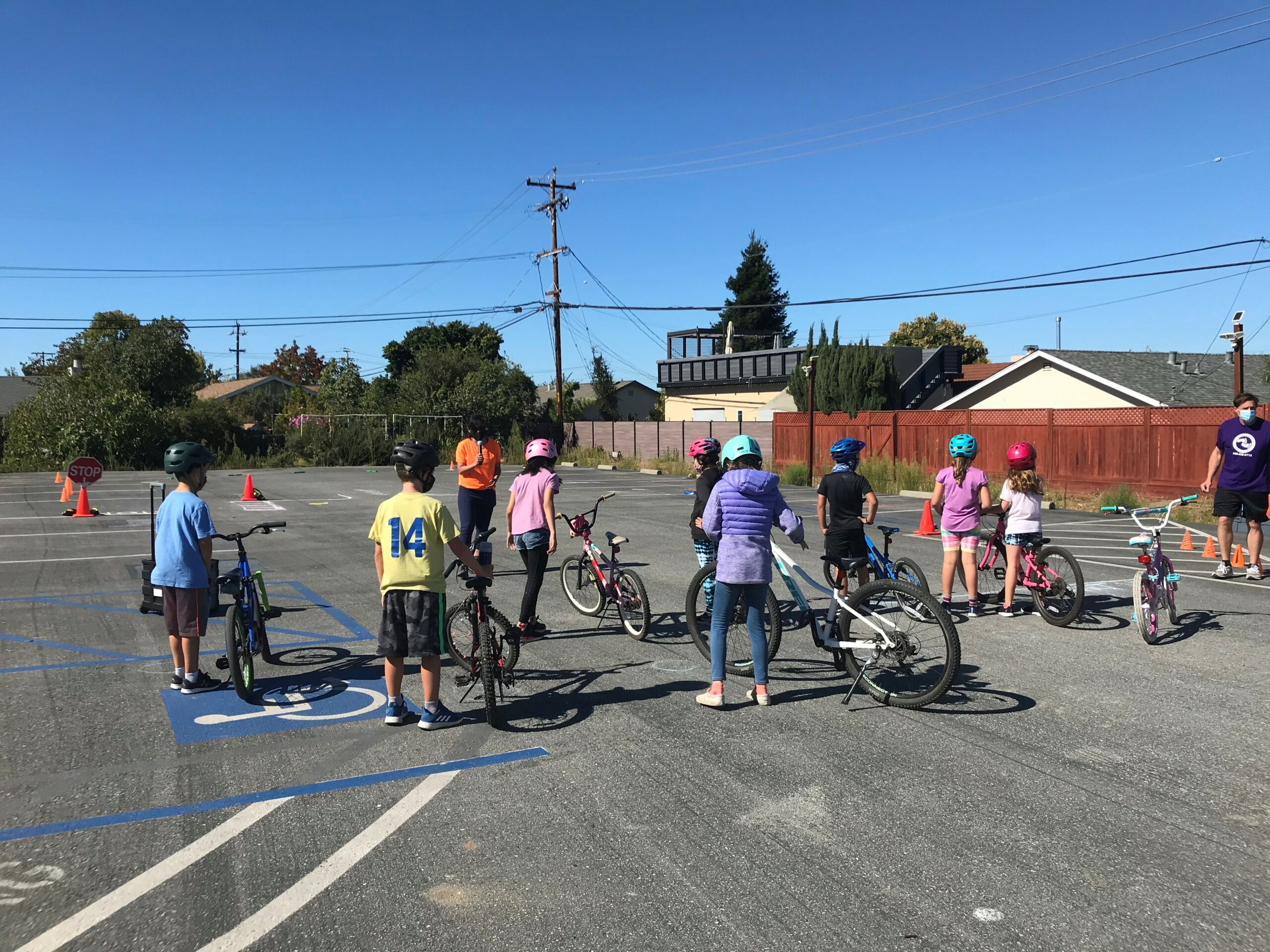 Image of kids standing in parking lot on bikes with helmets