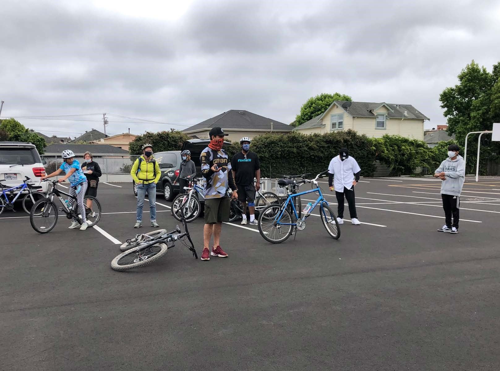 A group of people standing in a parking lot with bicycles during training