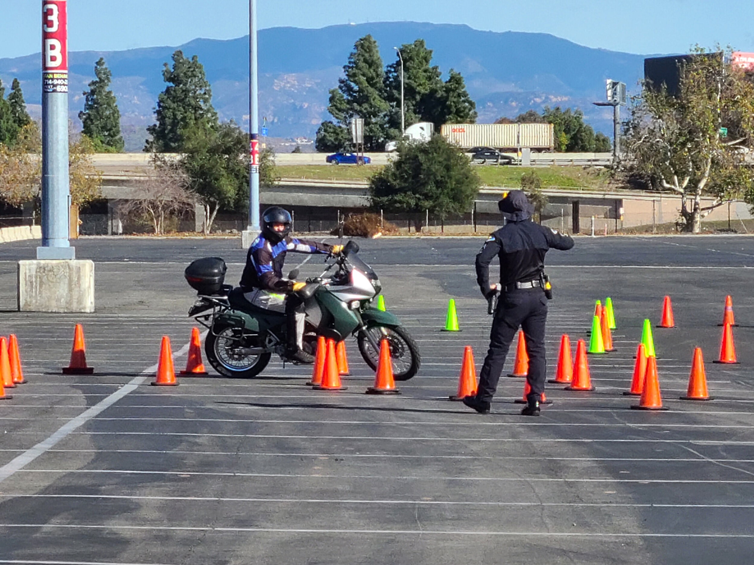 Motorcycle rider in parking lot with traffic cones